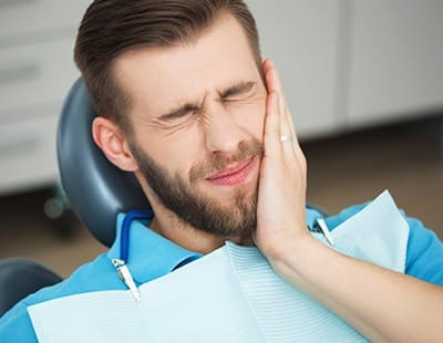 Man in dental chair holding cheek before emergency dentistry