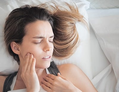 Woman in need of tooth extraction holding cheek in pain